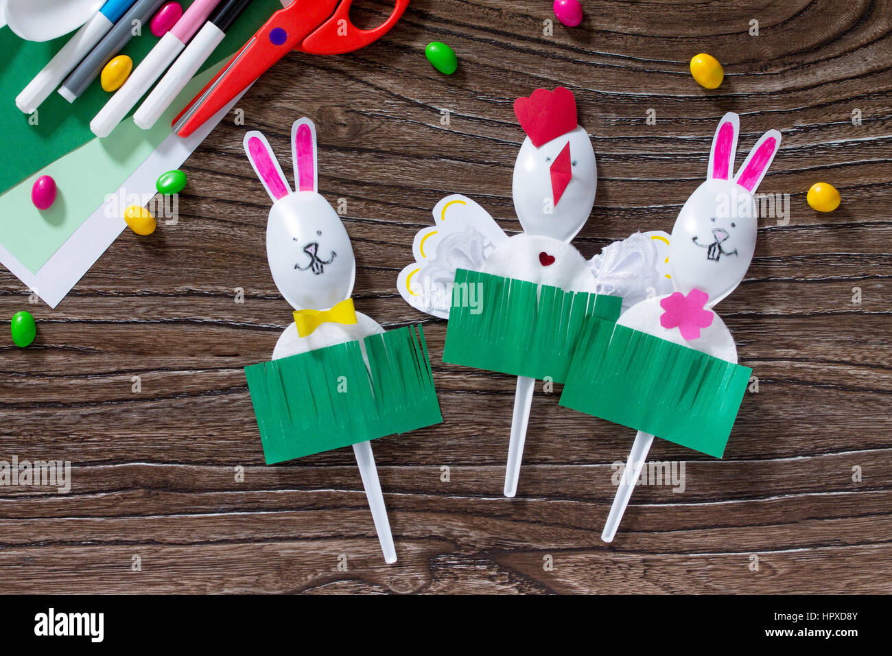 The child creates an easter gift toy easter bunny paper glue and the child creates an easter gift toy easter bunny paper glue and plastic spoons on a wooden table made by hand childrens art project needlework negle Images