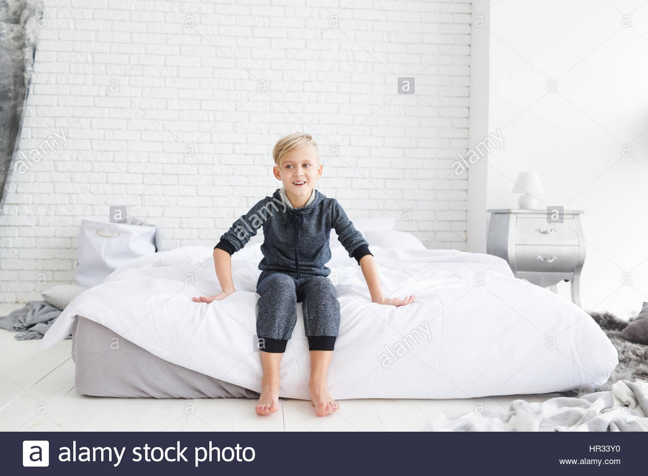 Little Boy In Gray Pajamas Sitting On A Bed Boy Having