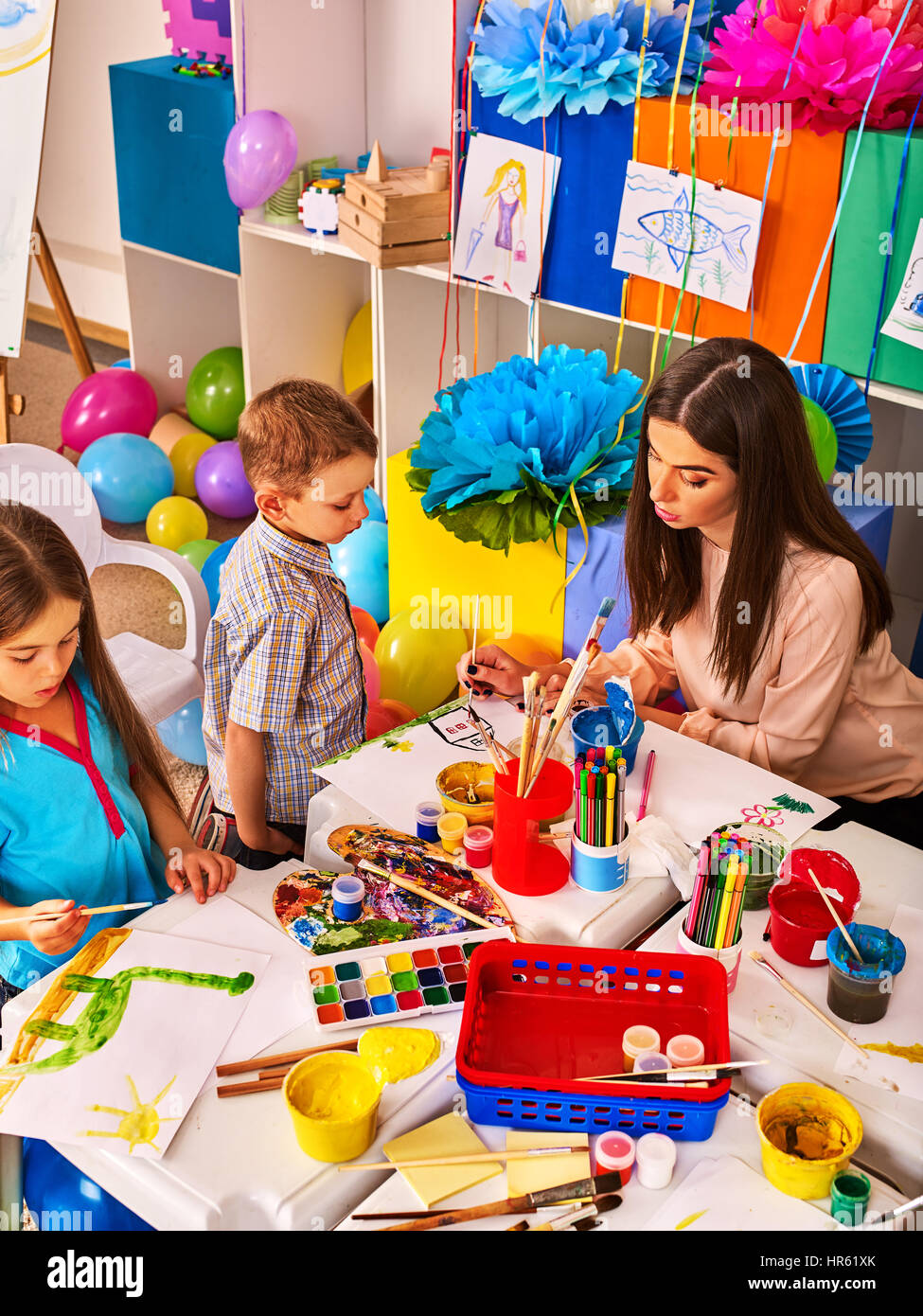childrens paint brushes and children painting and drawing in kids club craft lesson in primary school kindergarten teacher and small students work t - Children Painting Images