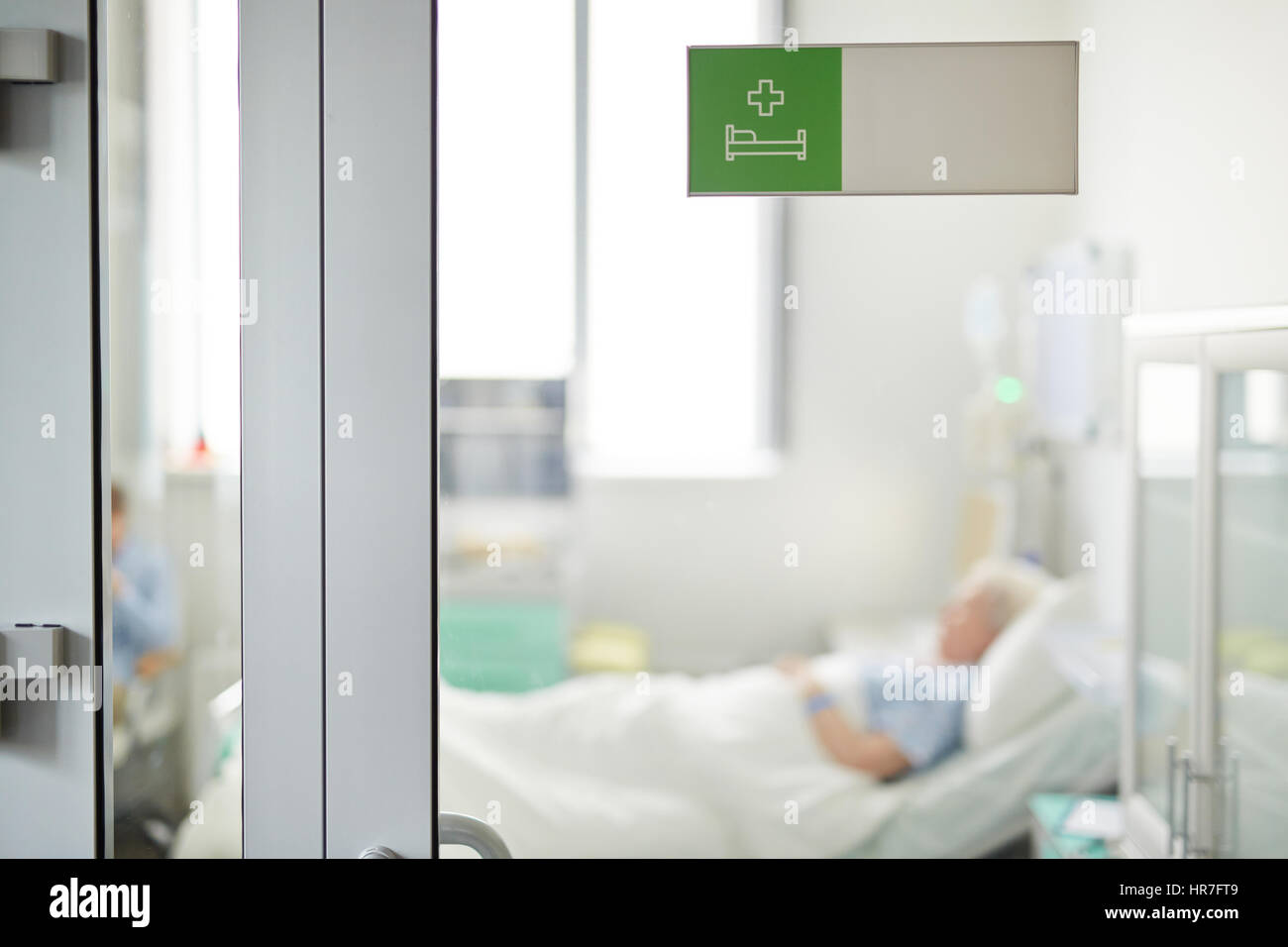 Hospital ward sign on closed glass door in clinic with blurred shape of senior patient lying on bed behind it & Hospital ward sign on closed glass door in clinic with blurred ...