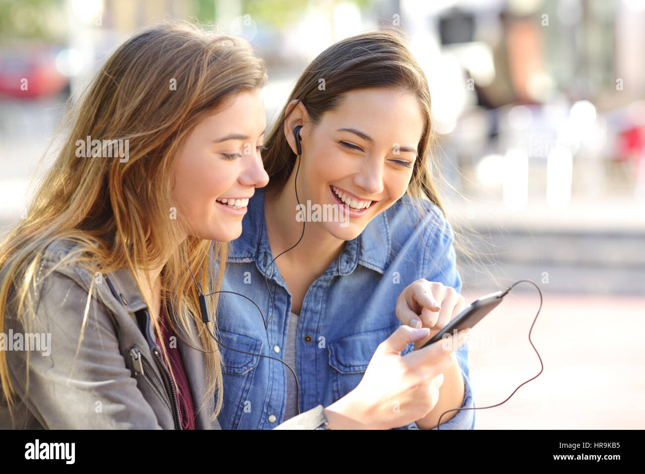 Two happy friends sharing a phone to listen music on line ...