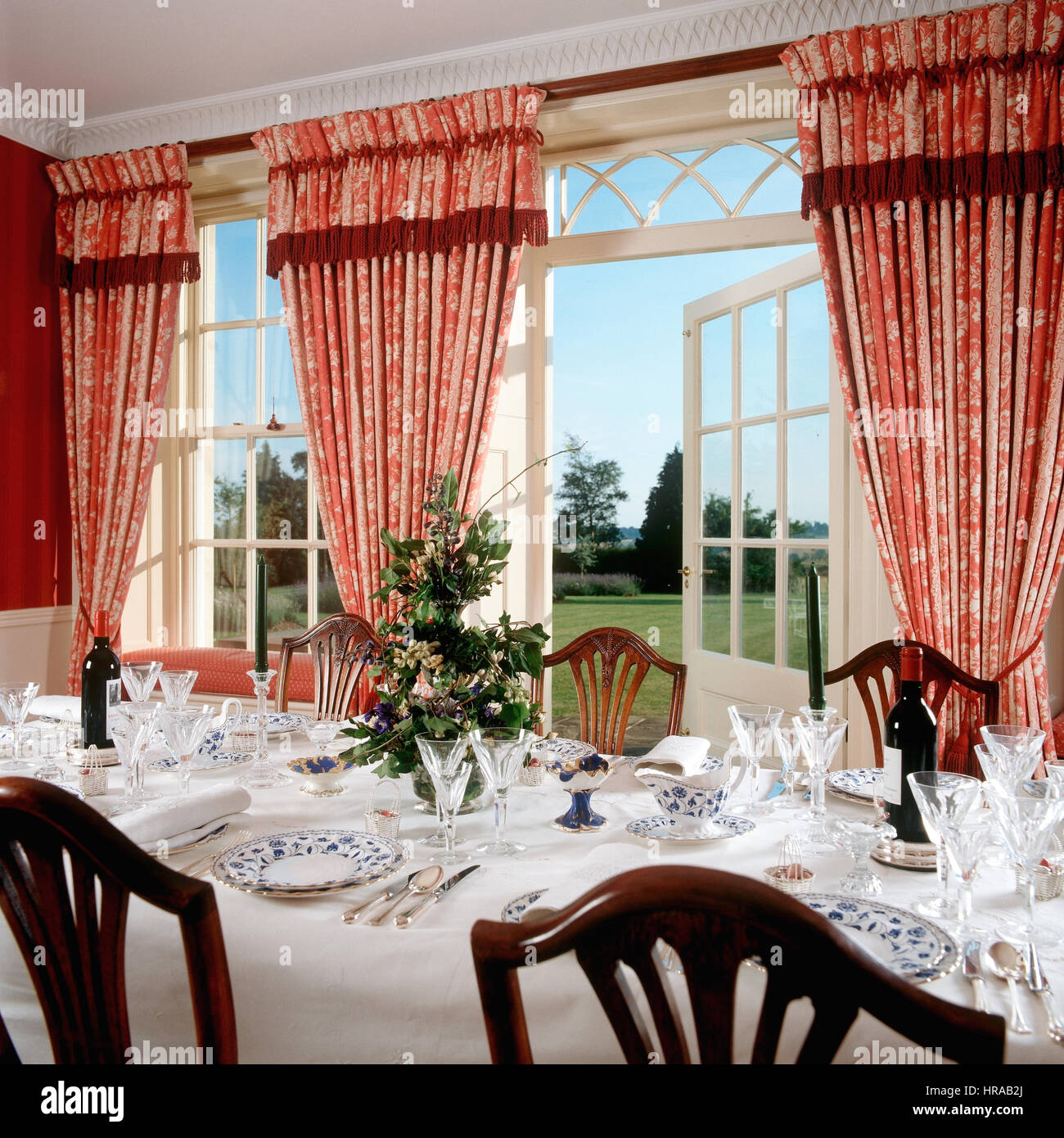 Red patterned curtains - China And Glassware In Dining Room With Red Patterned Curtains Framing Spectacular Views To Garden