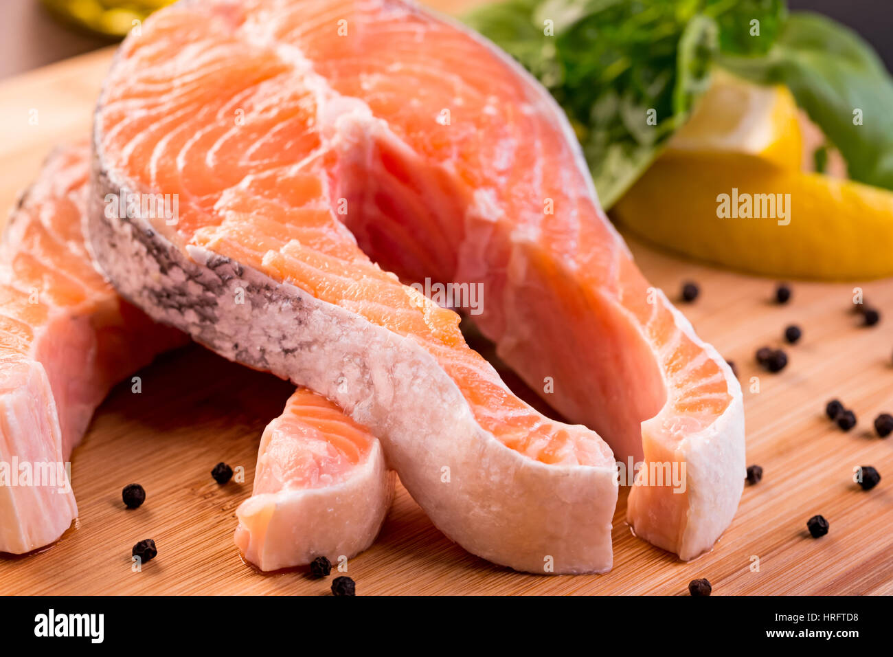 Raw fish fillet with lemon and basil on wooden cutting for Fish fillet board