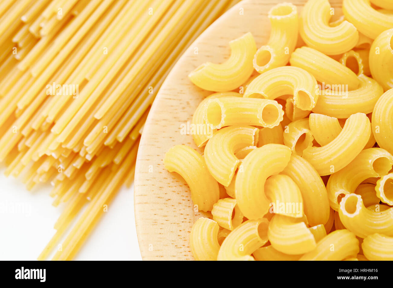 Raw Elbow Macaroni In Wooden Dish With Raw Pasta On White Background