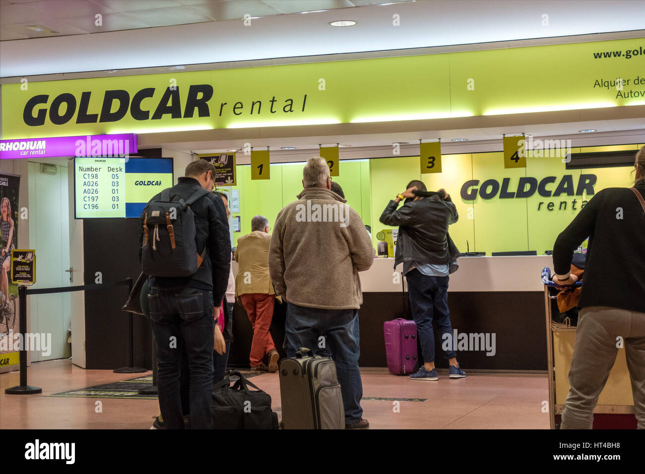 Goldcar gold car hire rental car rentals desk at malaga airport with customers in line