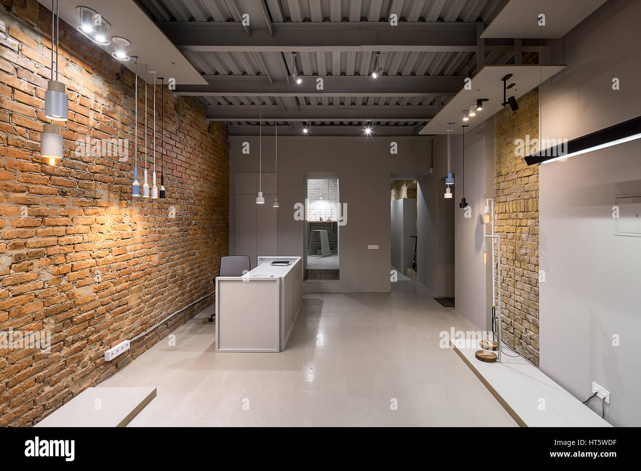 office in a loft style with brick and gray walls. there are many