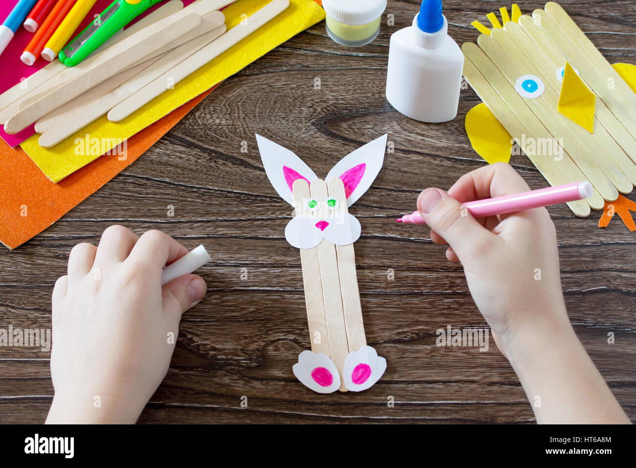 The child draws details of gift items childrens easter gift toy the child draws details of gift items childrens easter gift toy chicken and easter bunny hand made the project of childrens creativity needlewor negle Gallery