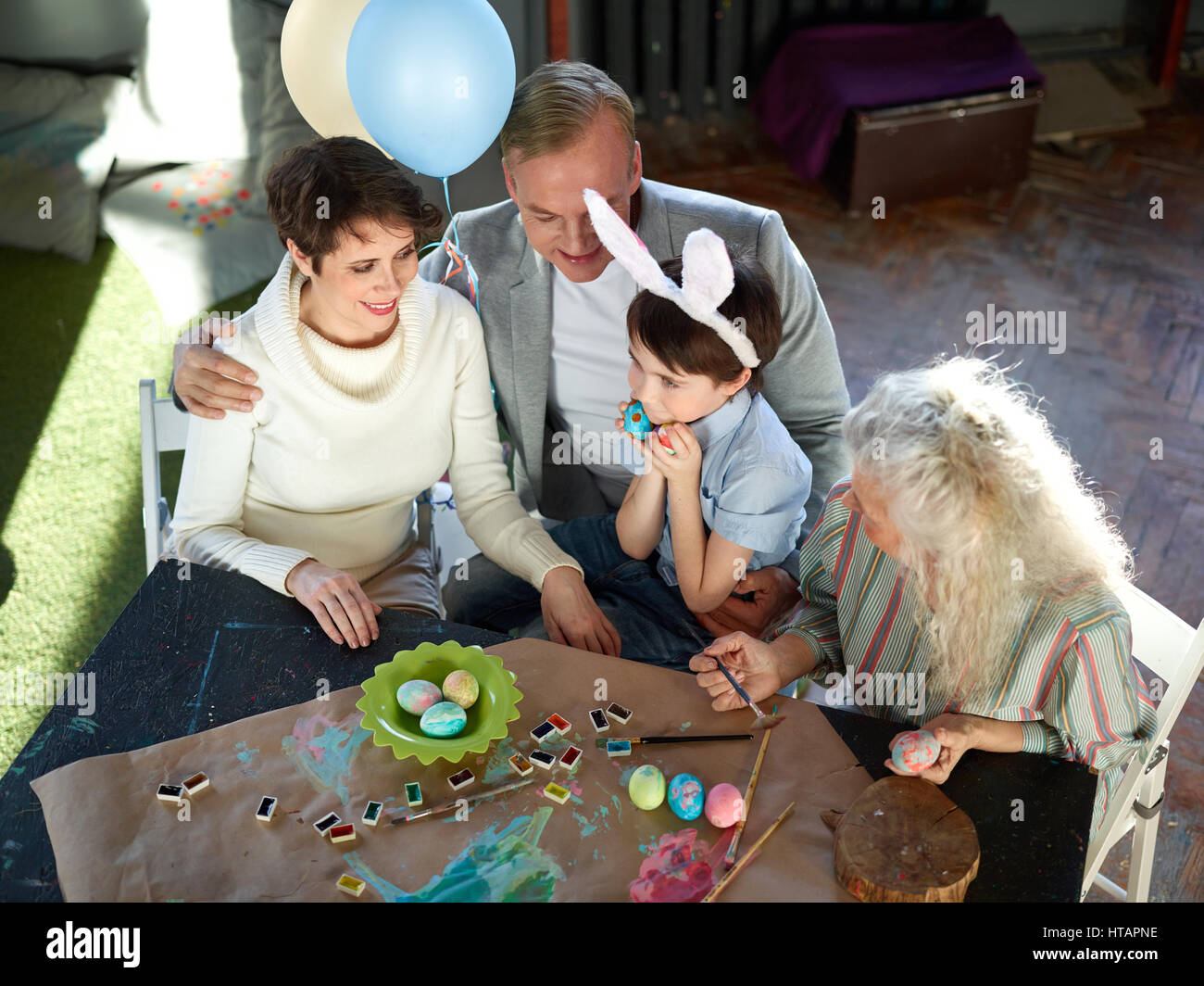 granny boy Cute bunny boy with two painted eggs, his parents and granny sitting by  table