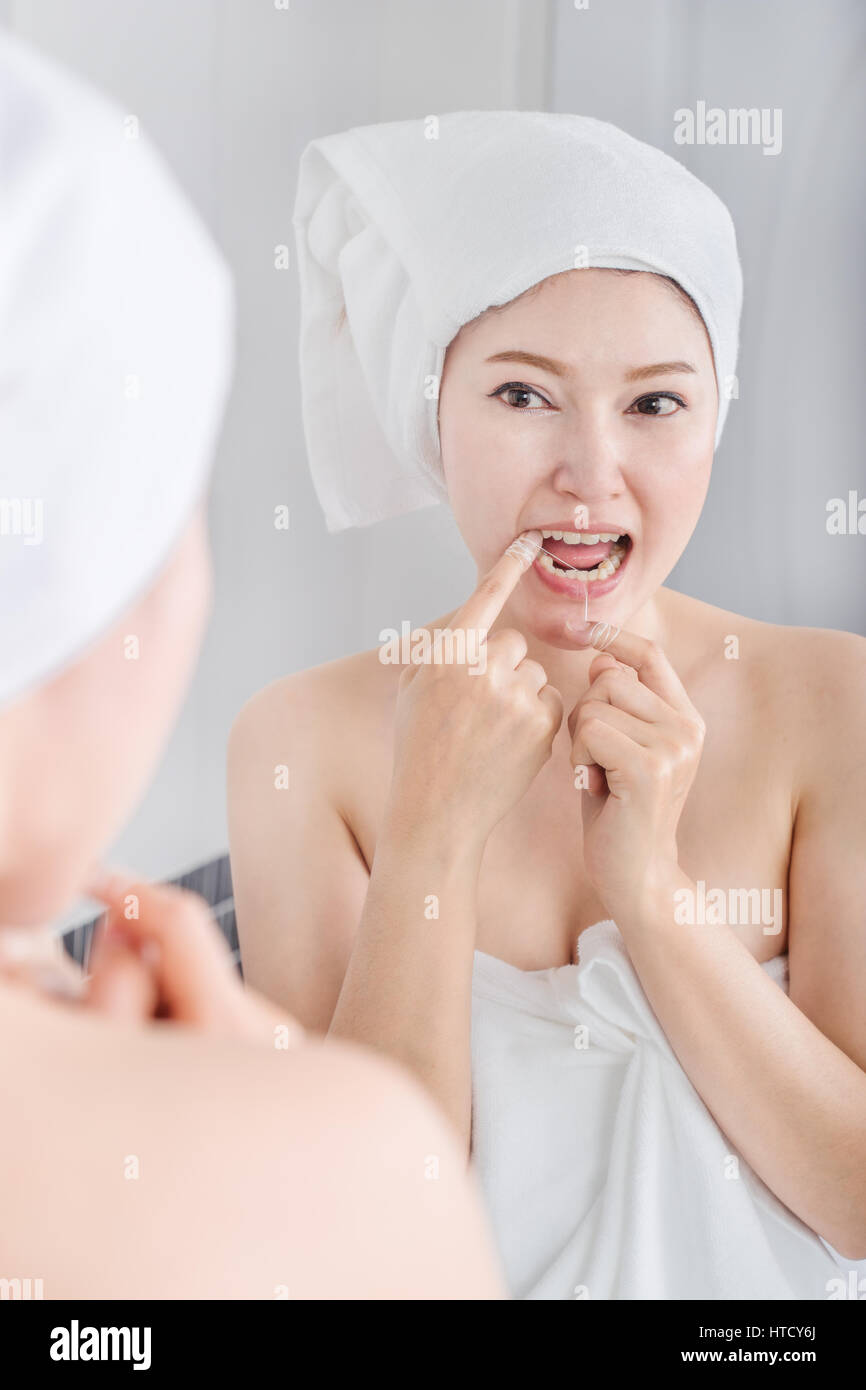 Woman Use Dental Floss White Healthy With Mirror In The Bathroom