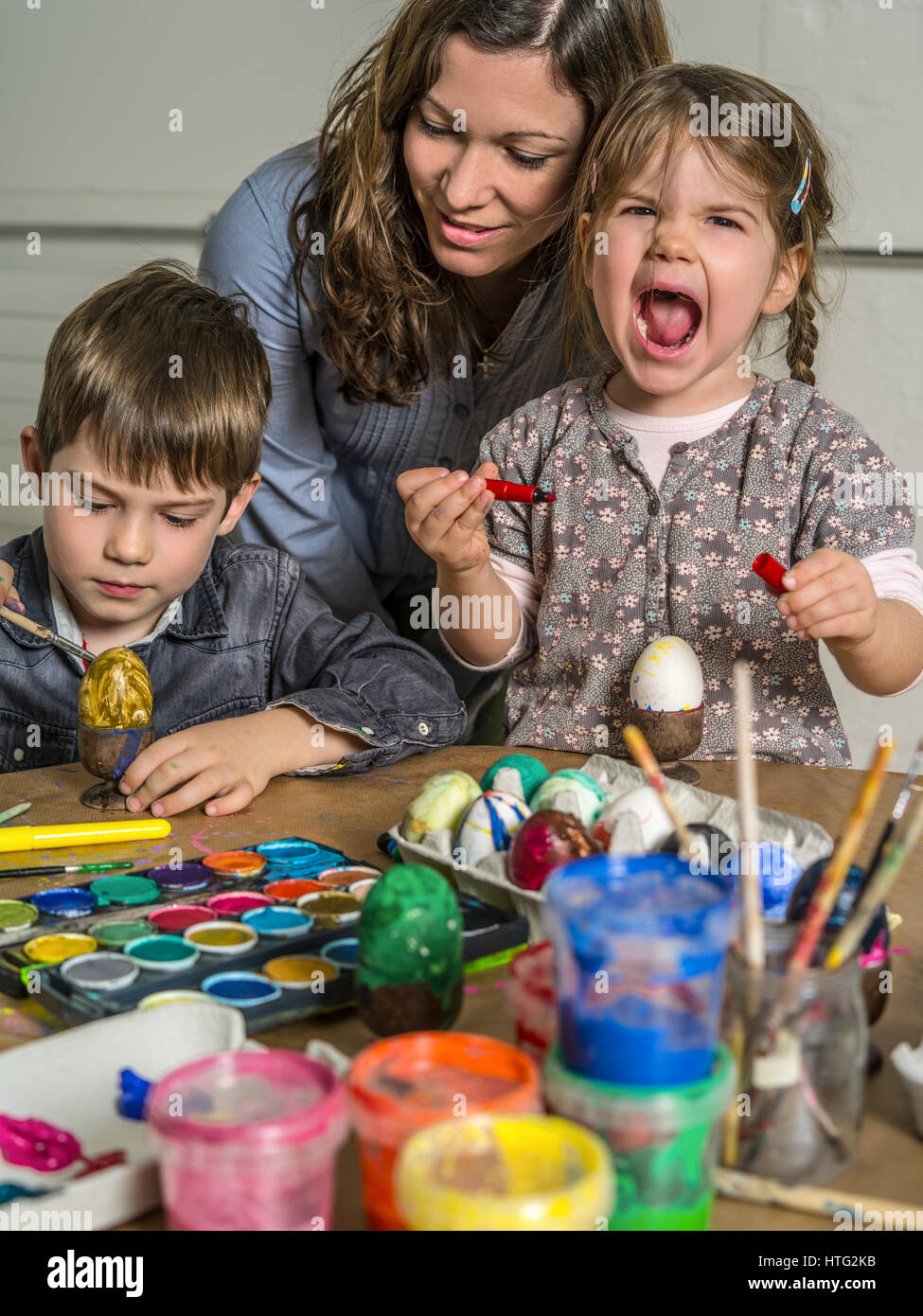 Photo of a mother and her children painting and decorating stock photo of a mother and her children painting and decorating hard boiled eggs for easter ccuart Gallery