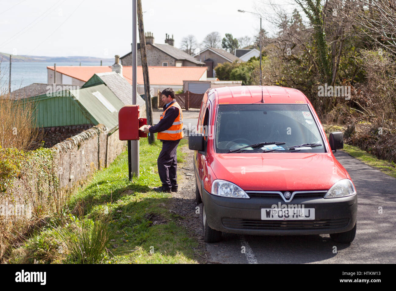 Postman collecting mail from mailbox in rural scottish village of