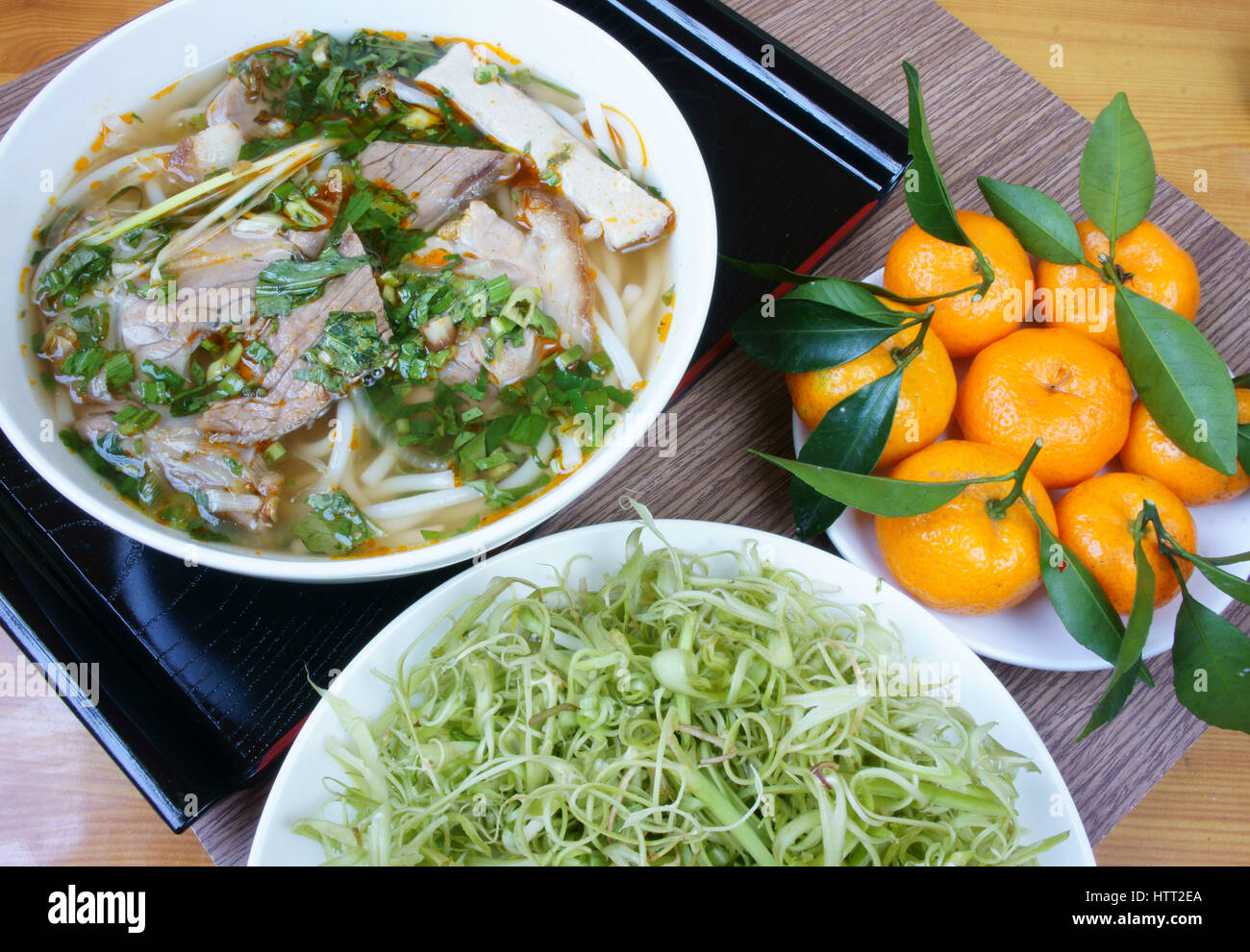 Stock Photo - Bun bo Hue is popular Vietnamese soup contain rice vermicelli (bun) and beef, this is delicious street food or meal, salty noodle bowl with vegetables