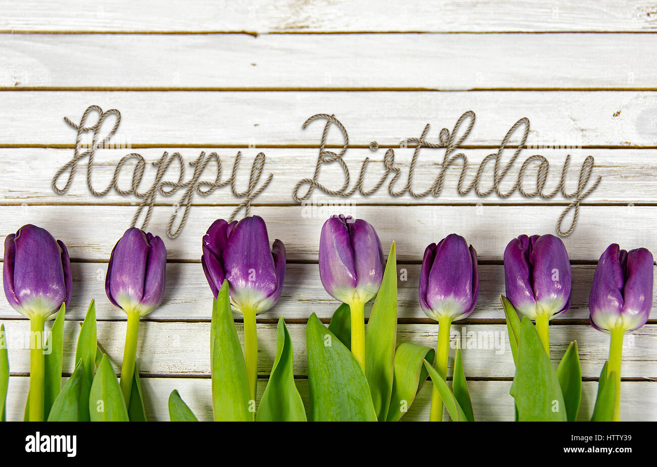 Happy birthday message in rope design with purple tulips on stock stock photo happy birthday message in rope design with purple tulips on whitewashed wood dhlflorist Gallery