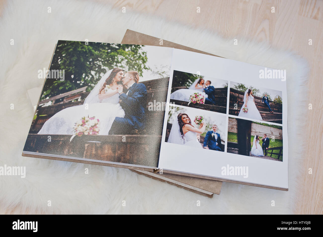 Pages of wedding photobook or wedding album at carpet on wooden ...