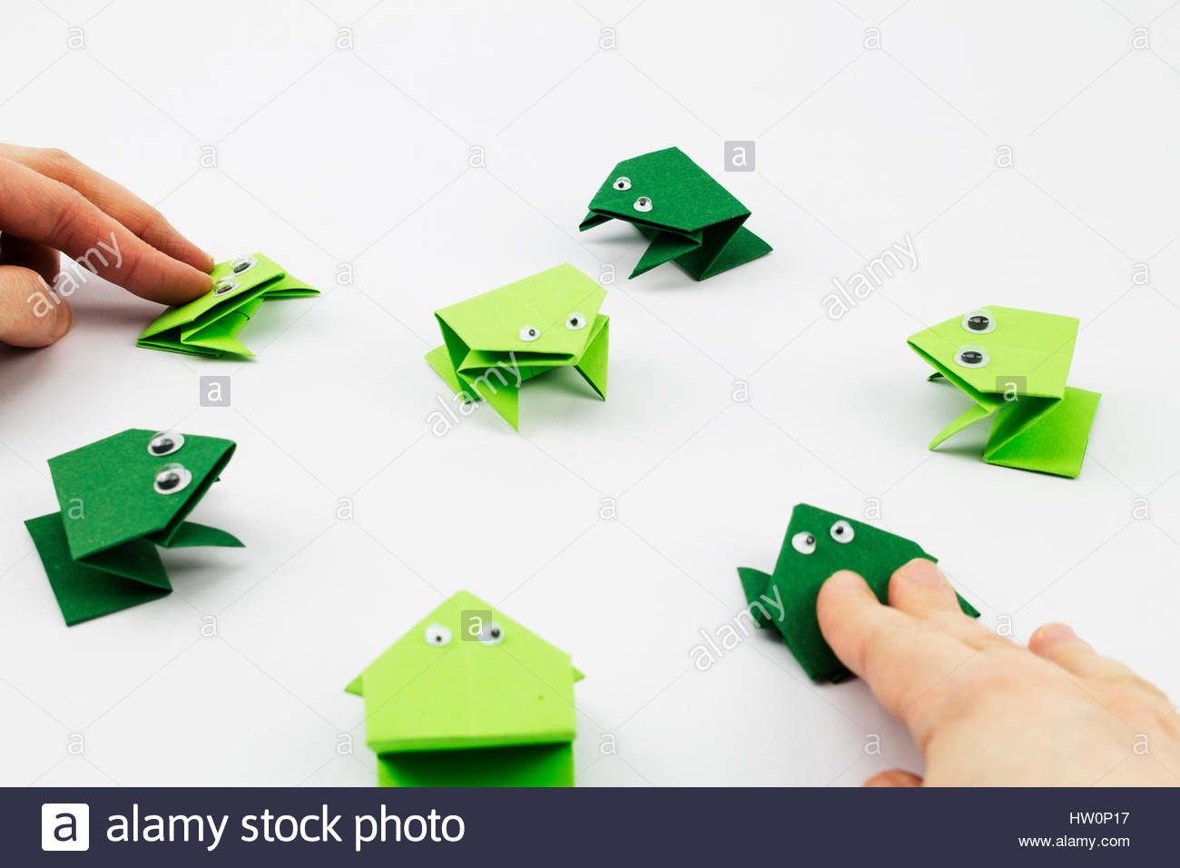 Hands playing the jumping frog game made from origami stock photo hands playing the jumping frog game made from origami jeuxipadfo Images