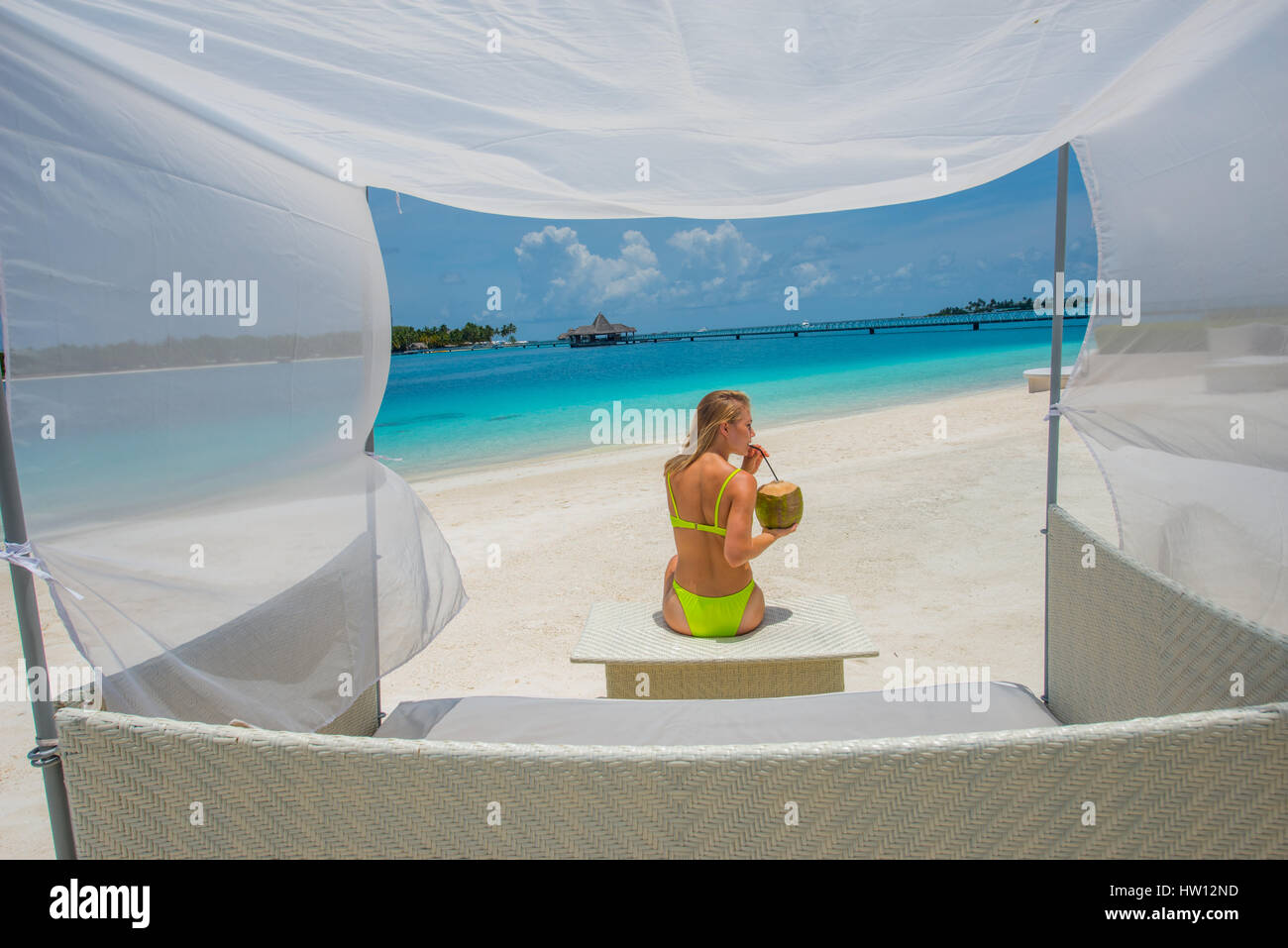 Males Rangali Island. Conrad Hilton Resort. Woman sitting in canopy chair on the beach. (MR & Males Rangali Island. Conrad Hilton Resort. Woman sitting in ...