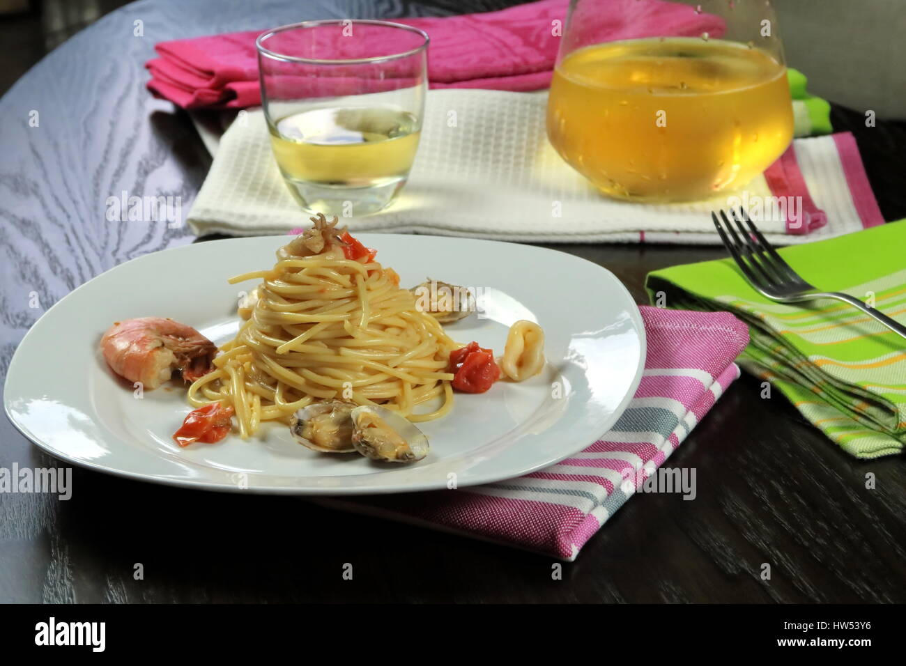 seafood pasta in white dish on colorful kitchen cloths and cool
