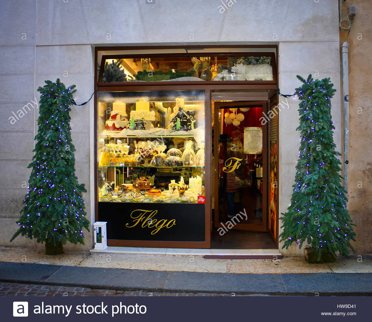 Traditional Christmas cakes in small shop window  decorative trees outside    Verona  Italy. Traditional Christmas cakes in small shop window  decorative trees
