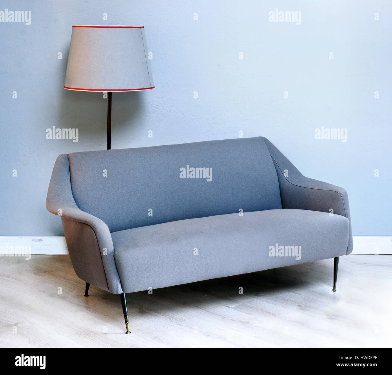 Upholstered Fabric Grey Two Seater Fifties Sofa With Thin Metal Legs With A  Matching Grey Lampshade On A Standing Or Floor Lamp In The Background Agai