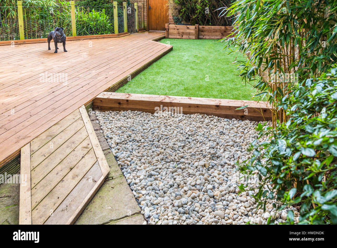 A Section Of A Residntial Garden, Yard With Wooden Decking, Patio Over A Fish  Pond, A Section Of Artificial Grass And An Area Of Stone Pebble. There I