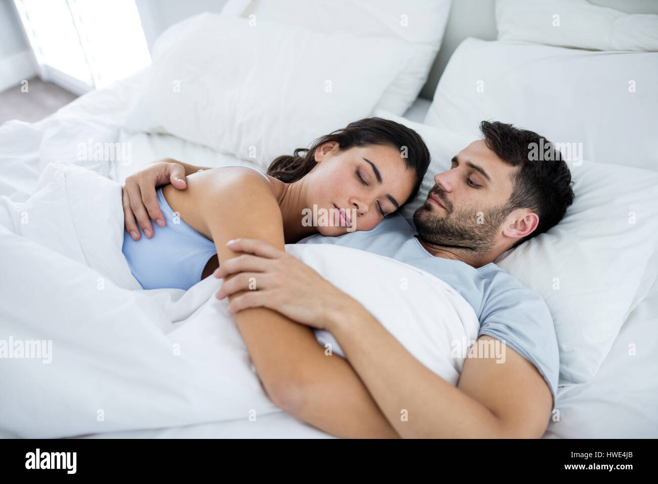 Young romantic couple sleeping on bed    in bedroom. Young romantic couple sleeping on bed    in bedroom Stock Photo