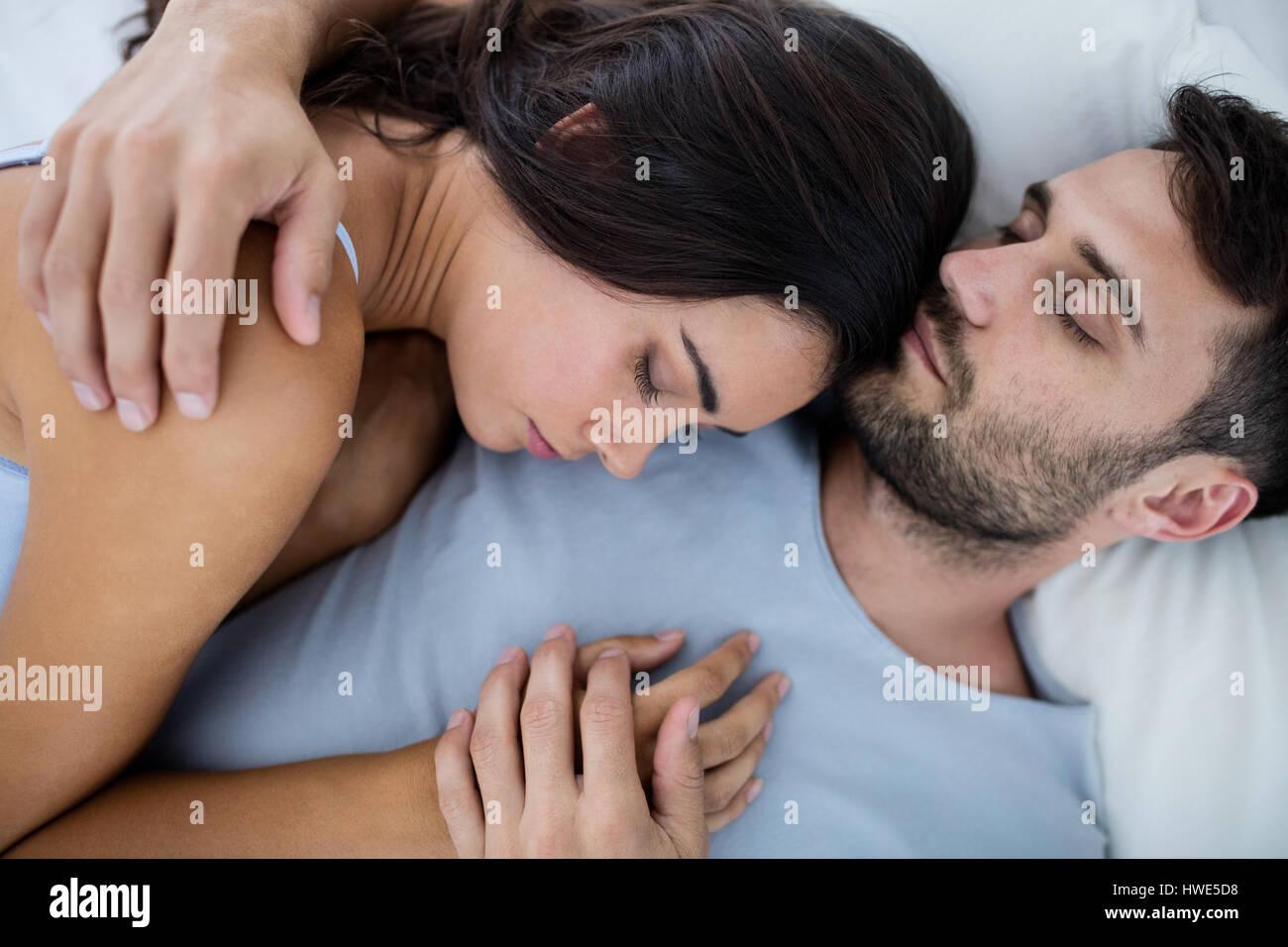 Stock Photo   Young romantic couple sleeping on bed    in bedroom. Young romantic couple sleeping on bed    in bedroom Stock Photo