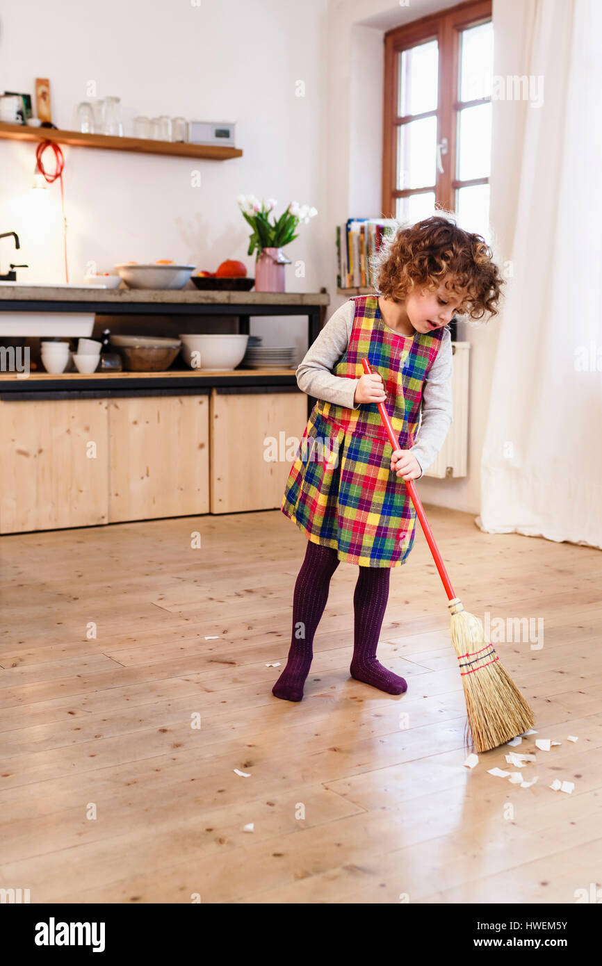 Sweep the kitchen floor - Cute Girl Sweeping Kitchen Floor Stock Image