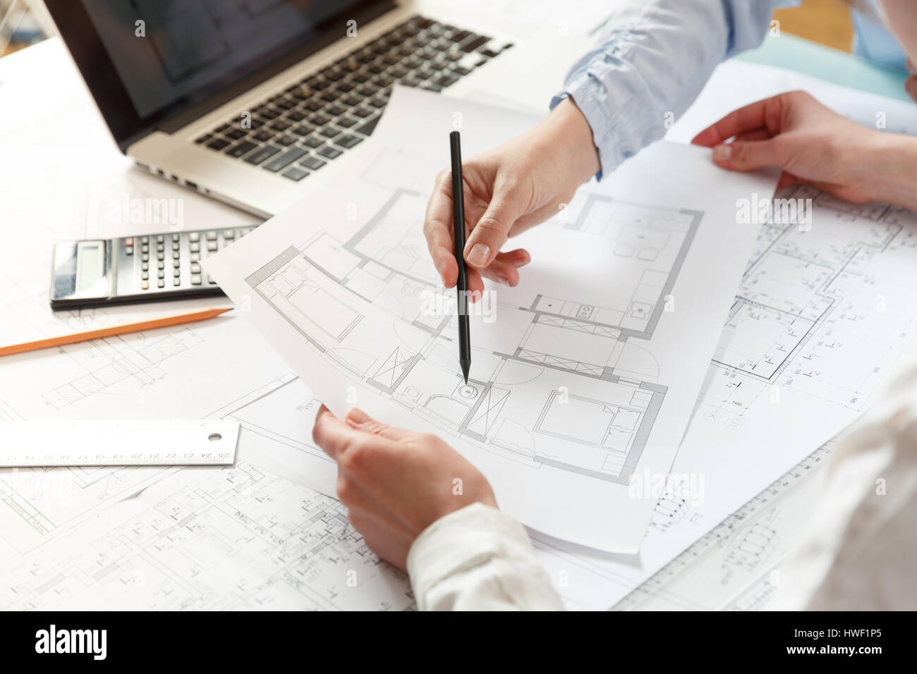 Young female architect and designer working on blueprint project ...