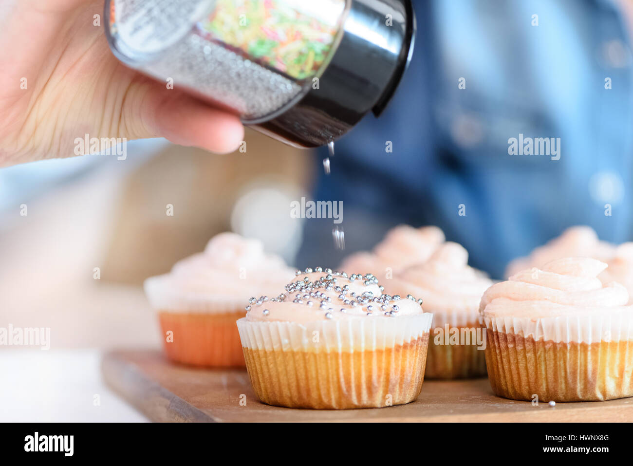 stock photo close up view of woman decorating cupcakes with confetti