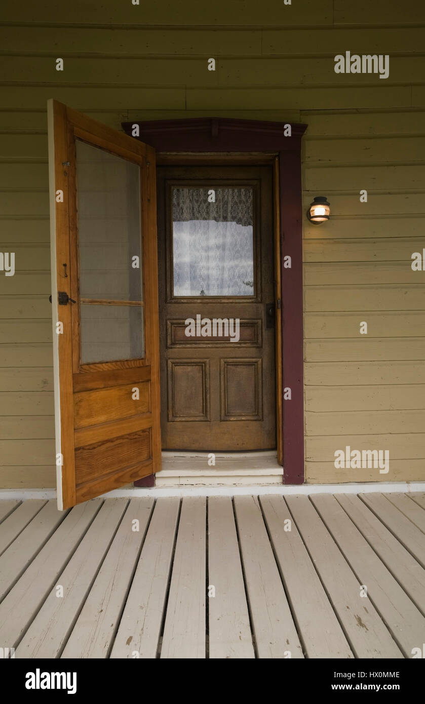 Veranda and opened brown wooden front entrance door on 1850 old ...