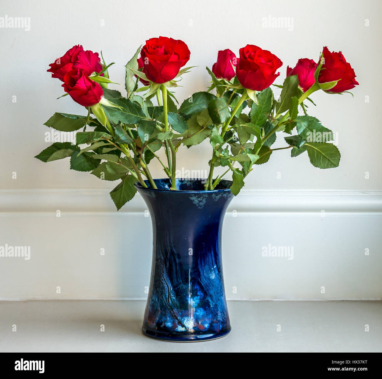 Simple arrangement of deep red roses in blue ceramic vase against simple arrangement of deep red roses in blue ceramic vase against plain neutral cream background reviewsmspy