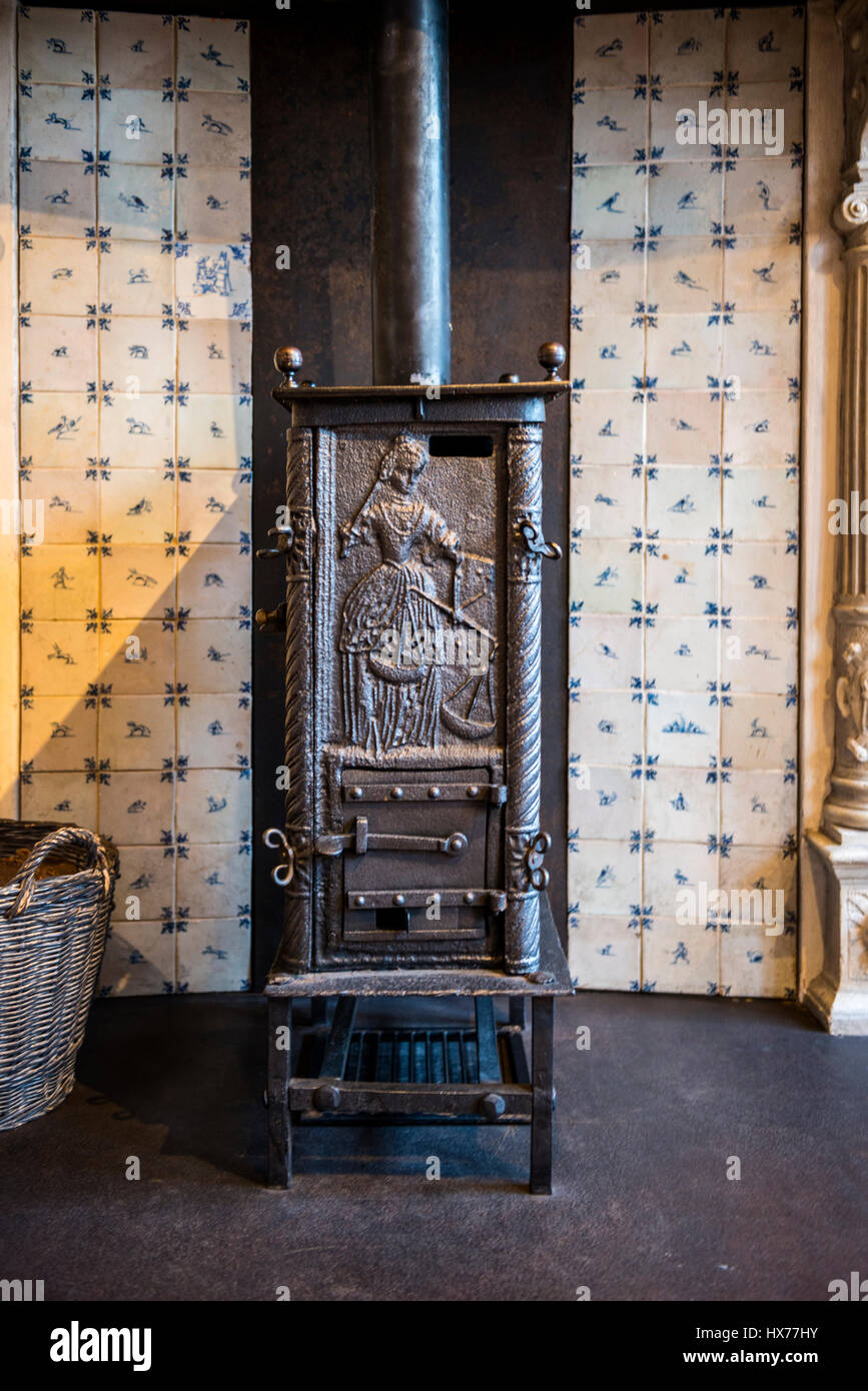 Old cast iron wood burning stove with an embossed door showing a ...