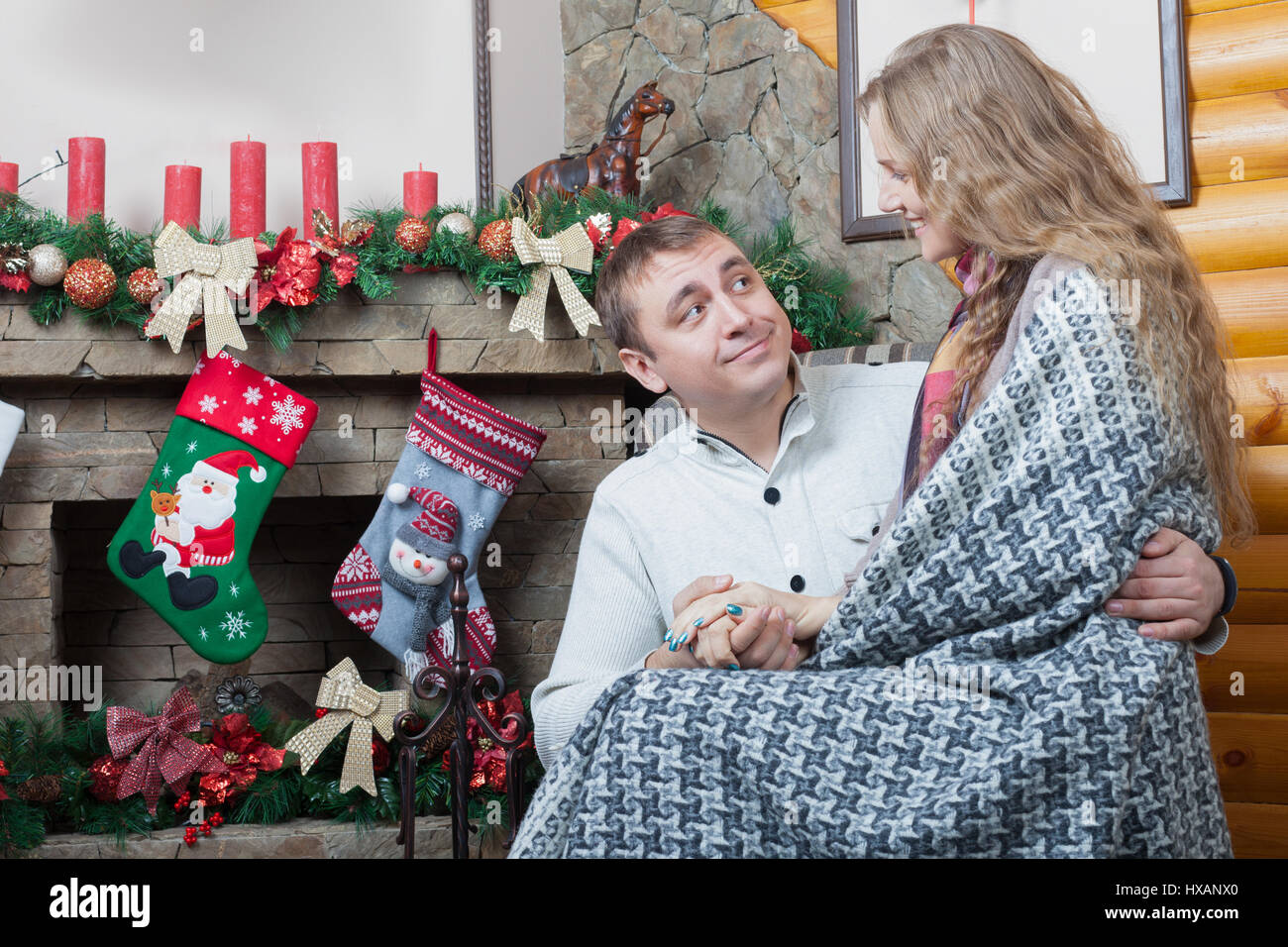 romantic pair sitting on the chair near a fireplace christmas