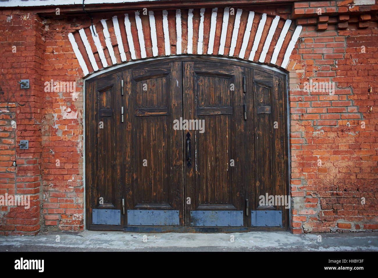 Old brown wooden door in red brick masonry. The old Soviet factory ...