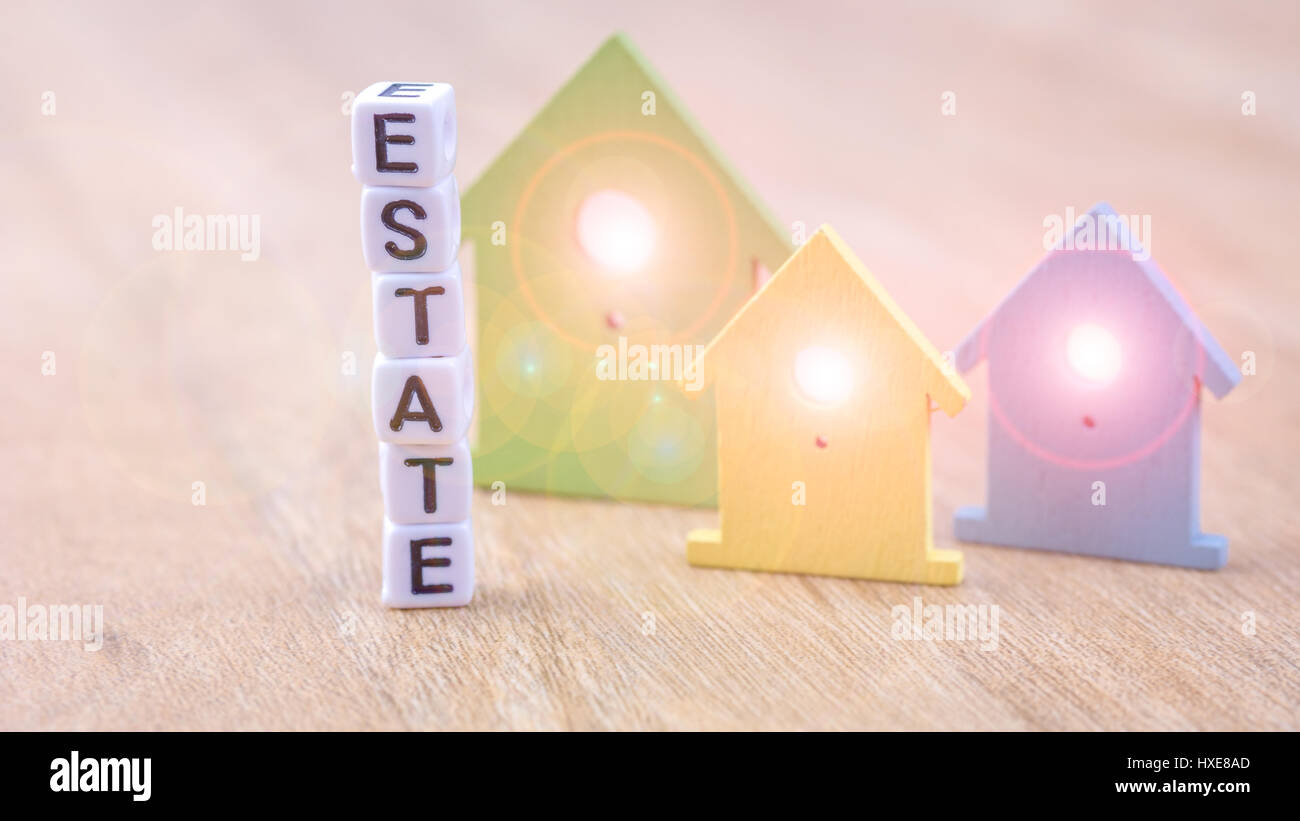 Estate word of cube letters behind coloured house symbols with estate word of cube letters behind coloured house symbols with light flares in windows on wooden surface buycottarizona