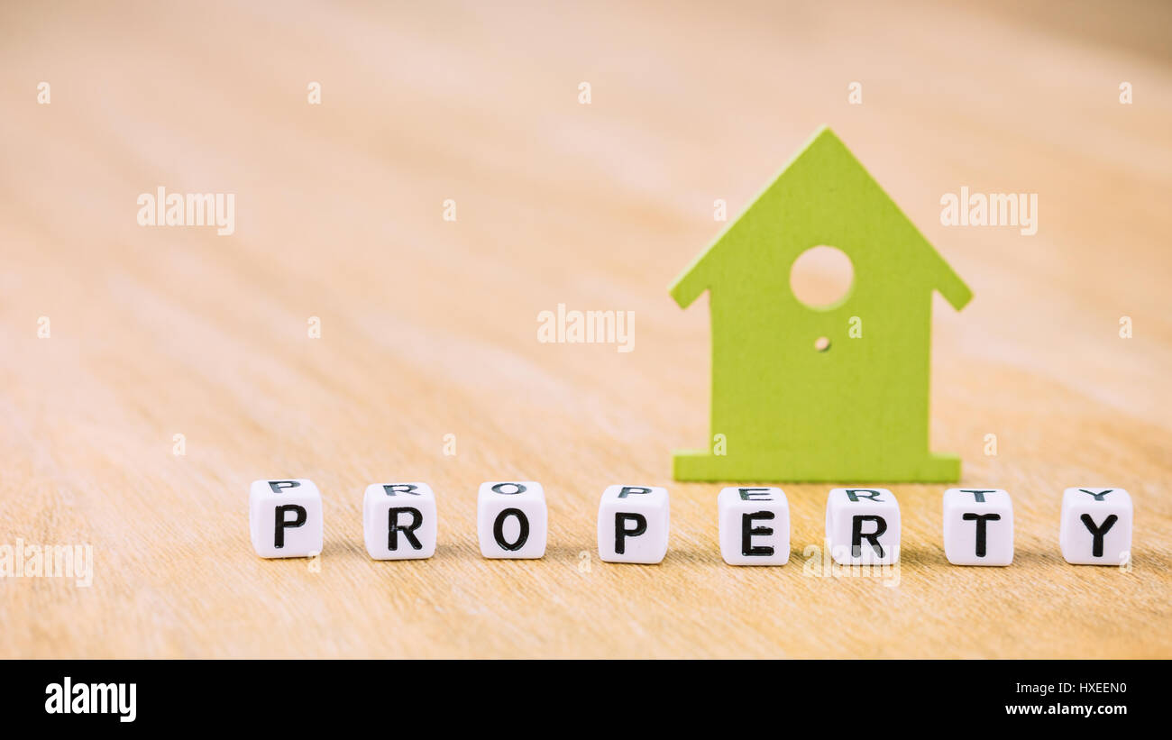 Property word of cube letters in front of green house symbol on property word of cube letters in front of green house symbol on wooden surface concept buycottarizona Images