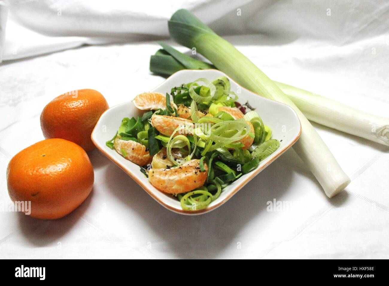 Stock Photo   Fusion Kitchen Easy Made Salad From Ripe Leek Onion And Sweet  Mandarine Under Spices And Olive Oil