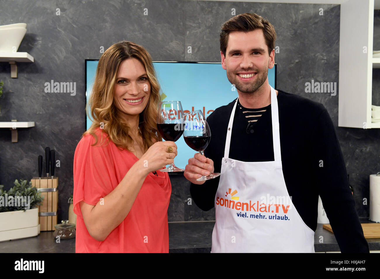 Alexander Keen (R) and host Stephanie Frohmann hold up glasses ... | {Küche & co 21}