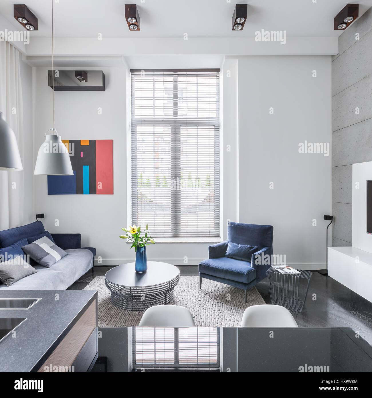 Stylish living room with big window and blue upholstered furniture ...