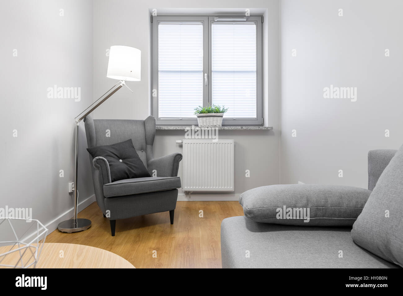 Bright living room with grey, upholstered armchair and sofa Stock ...
