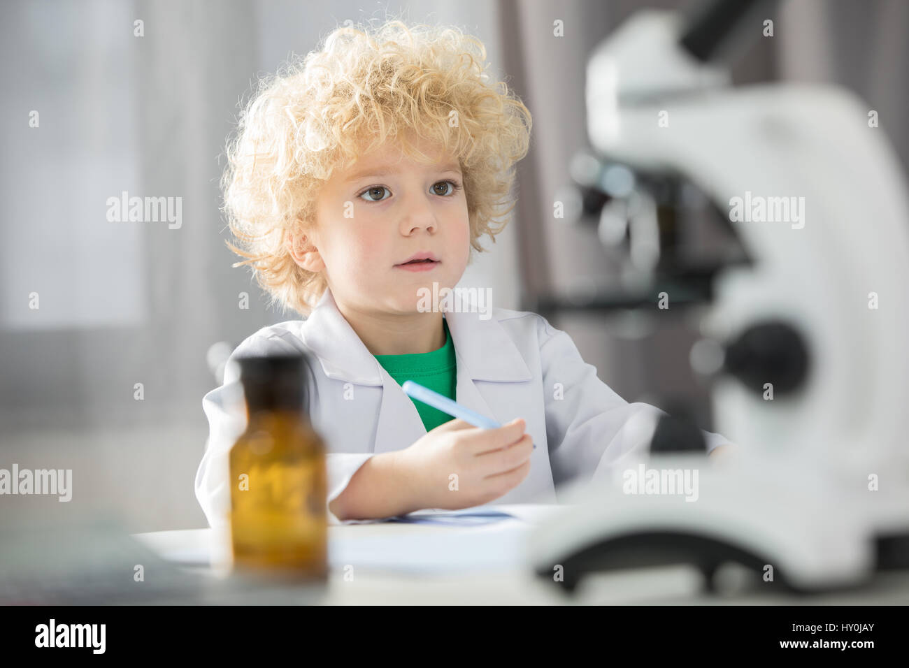 Schoolboy in white lab coat taking notes during scientific ...