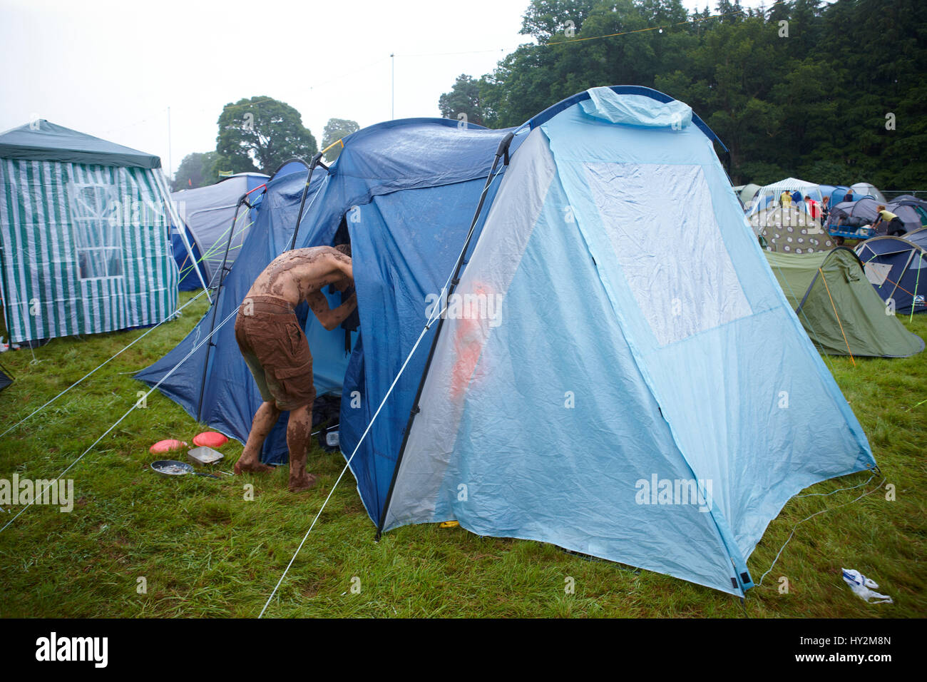 Muddy people going in a blue tent Green Man Festival Wales & Muddy people going in a blue tent Green Man Festival Wales Stock ...