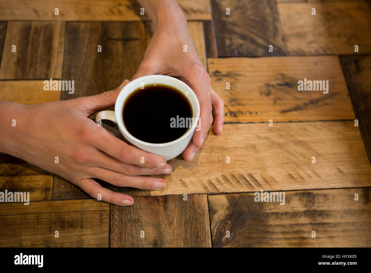 Overhead shot of man holding coffee cup at table in cafe stock overhead shot of man holding coffee cup at table in cafe geotapseo Gallery