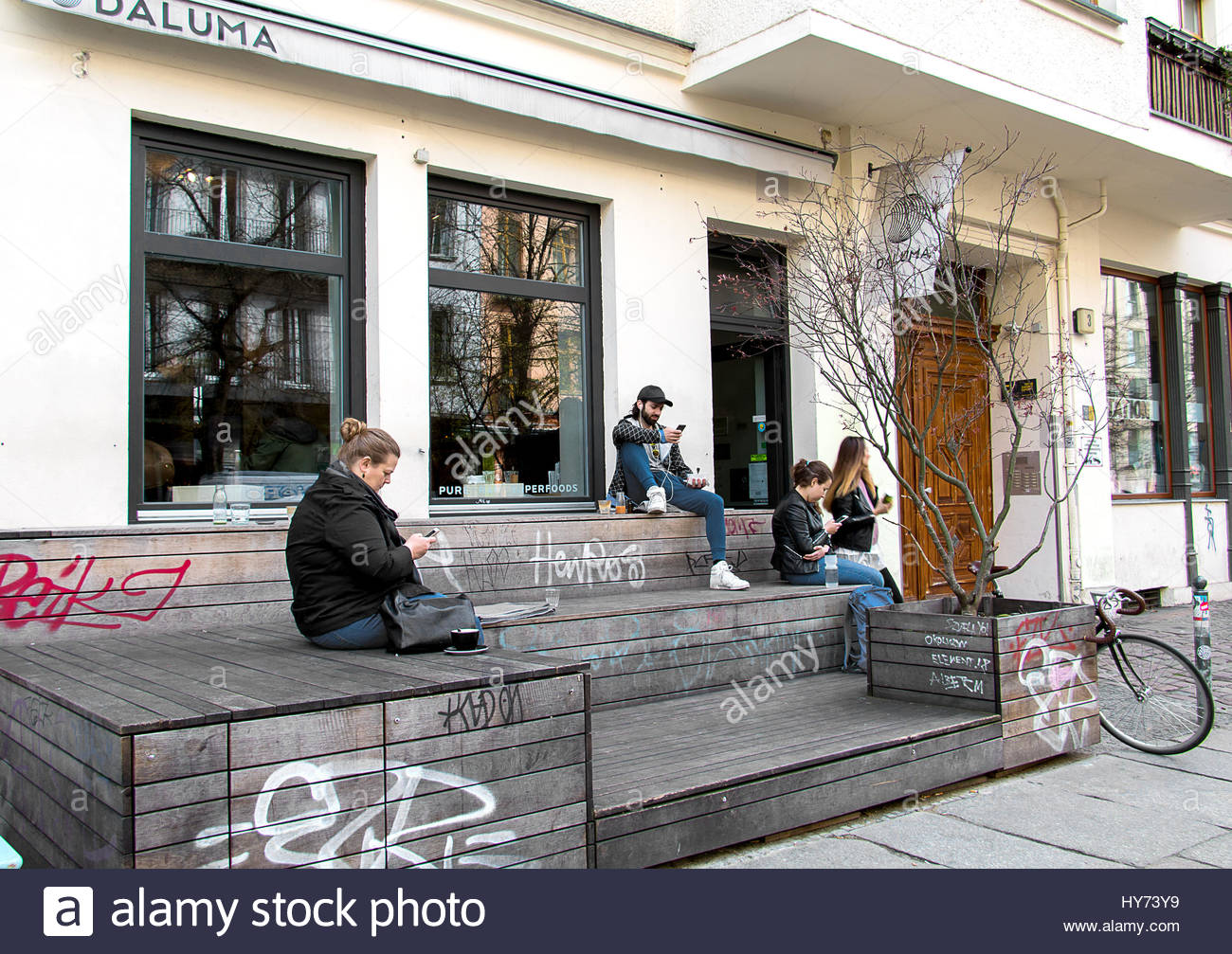 Hipster berlin coffee shop trendy young people coffeehouse texting smartphone looking at cell phone using iphone user