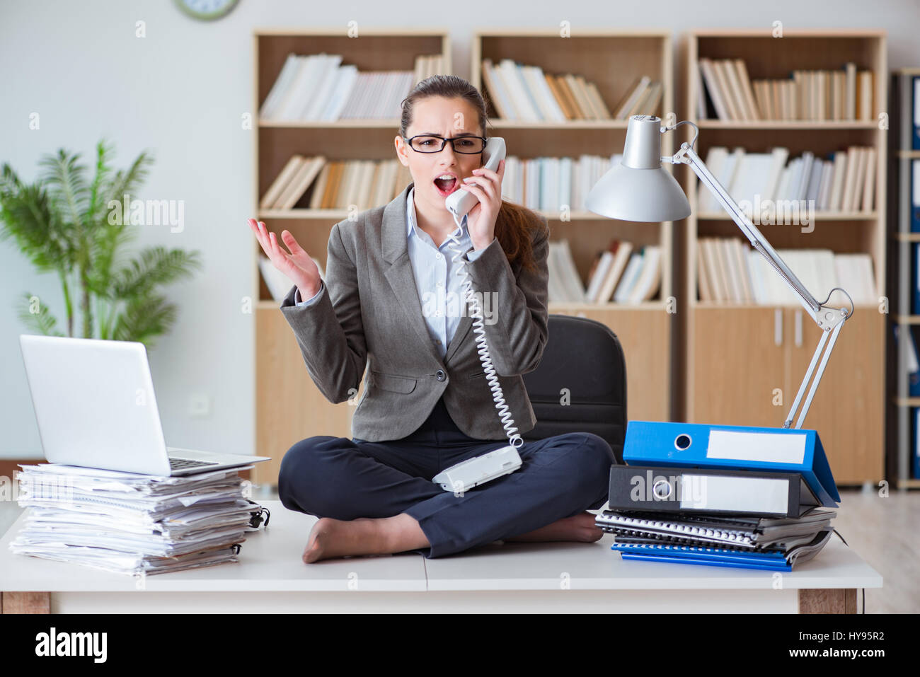 Busy angry businesswoman sitting on the desk in office Stock Photo ...