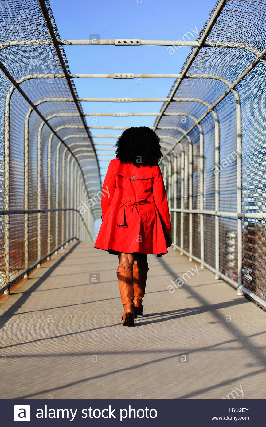Young woman in a red coat walking away on bridge Stock Photo ...