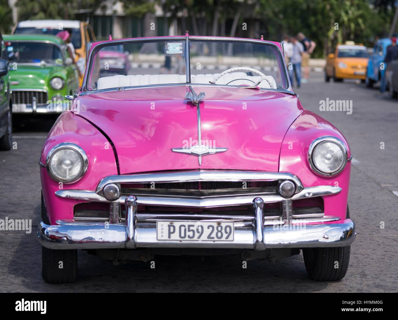 Old fashioned classic 1950s American car in vibrant pink colour ...