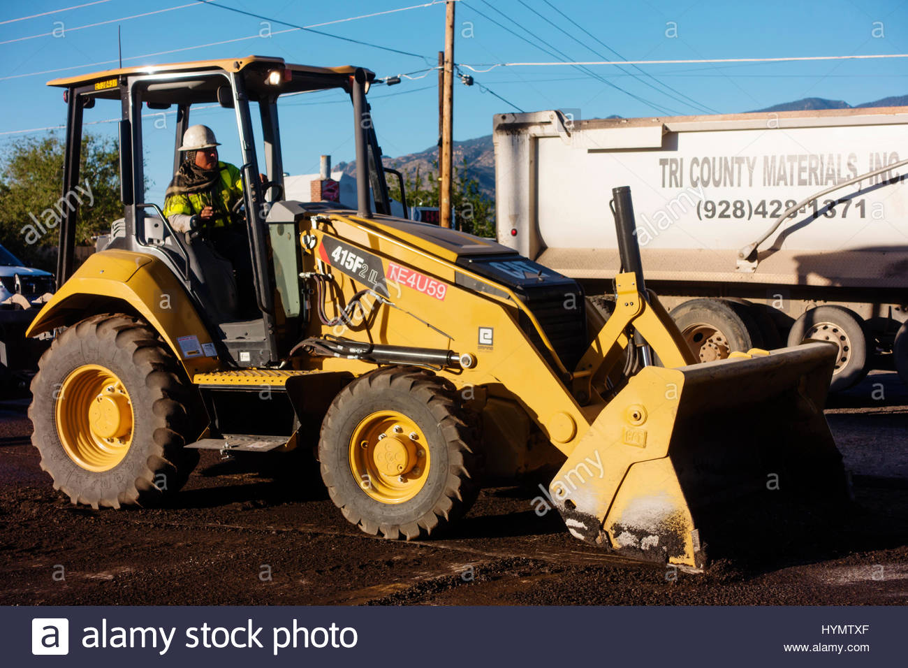 Caterpillar 415F2 loader working on road construction in Arizona operator visible Stock Photo