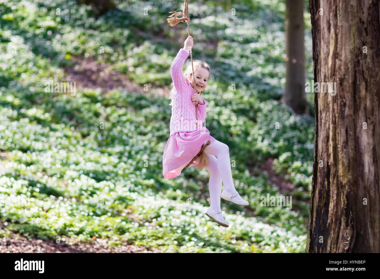 cute little in pink dress on tree swing in blooming