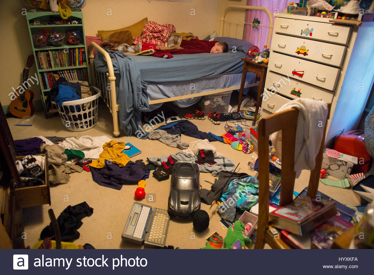 a young boy sleeps in his messy room stock photo royalty free image 137654366 alamy. Black Bedroom Furniture Sets. Home Design Ideas